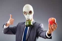 man with gas mask and apple