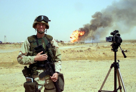 An American soldier stands near a 2006 oil field fire near Kirkuk