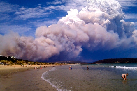 Smoke from a bushfire billows over beach goers at Carlton, about 20 kilometres (12 miles) east of Hobart.