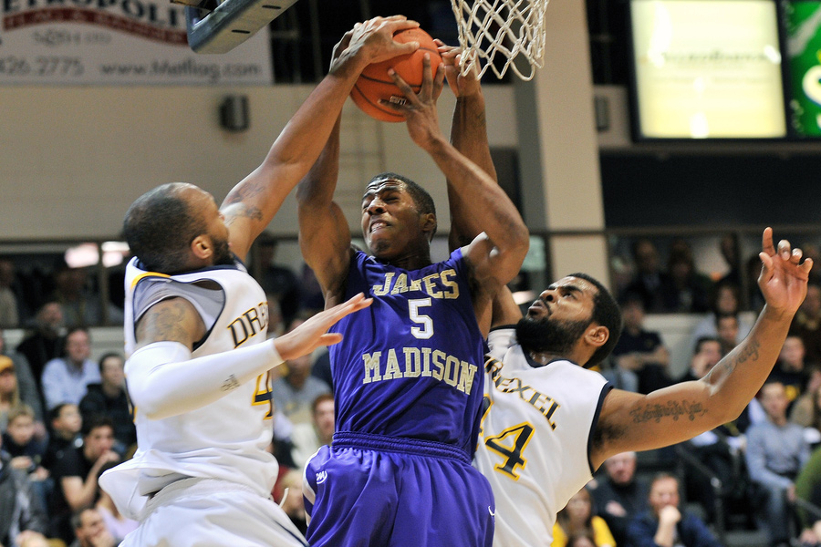 James Madison guard Alioune Diouf (5) battles for a rebound with two Drexel players during the NCAA basketball game between Drexel and JMU February 22, 2012 in Philadelphia