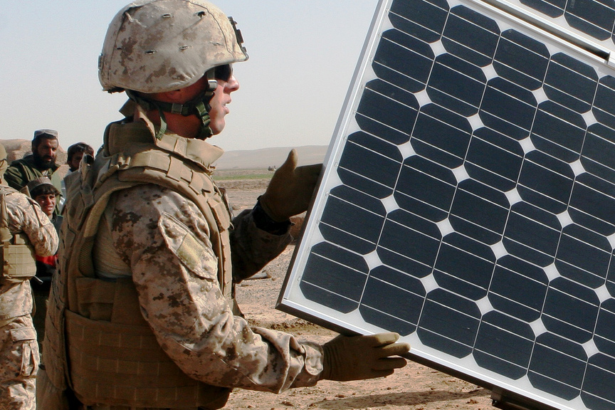 A United States Marine Corps engineer opens solar panels on a solar-powered water purification system in Afghanistan