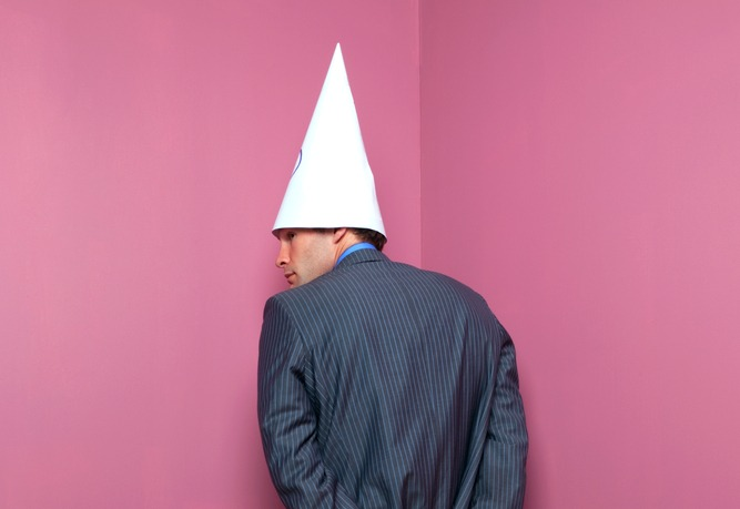 suited man in dunce cap