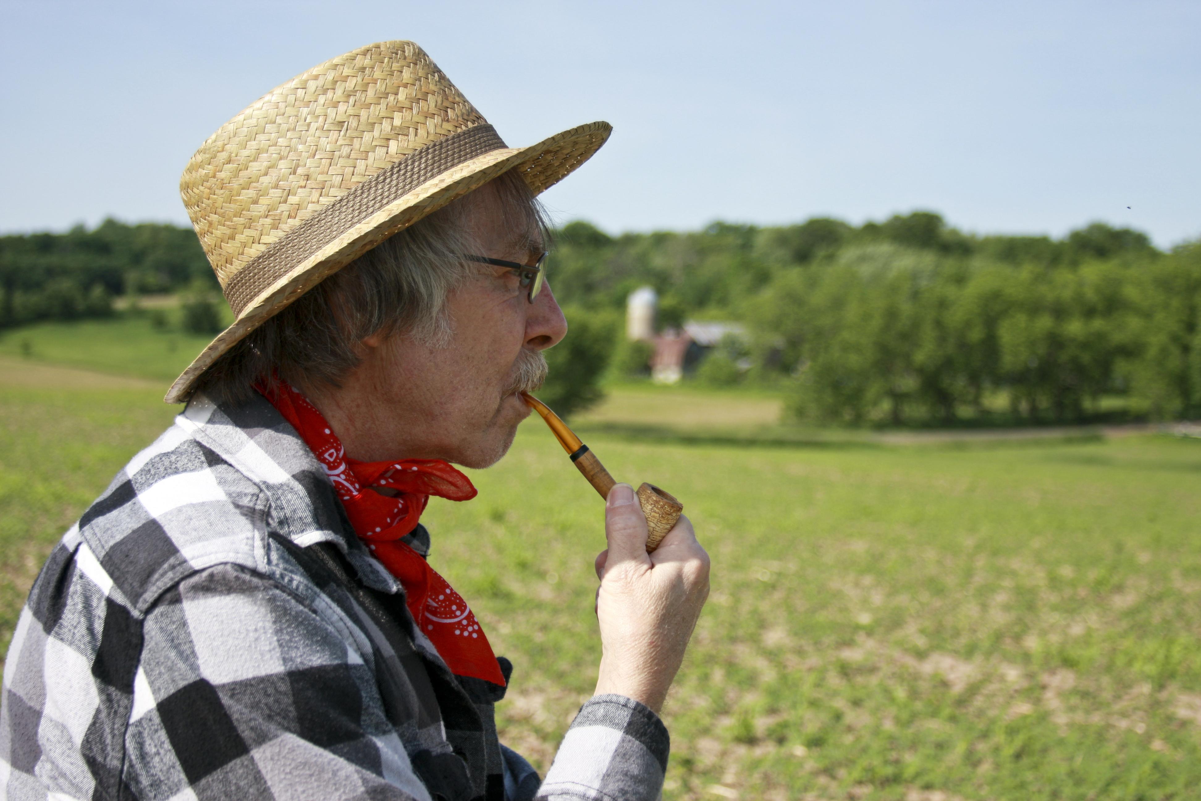 man smoking corn cob pipe