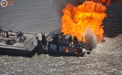 This photo, taken Wednesday, shows how close the barge is to the burning tug and pipeline. Inside the barge and not visible from the outside is 2,200 barrels of crude oil, according to the Coast Guard.