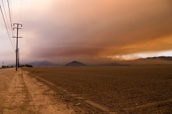 Smoke from the Springs Fire blows over a dry Californian landscape.