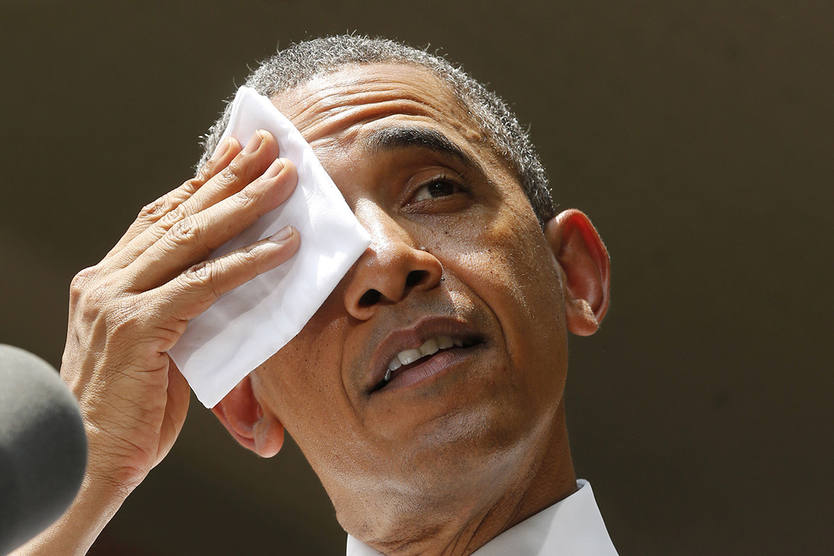 U.S. President Barack Obama wipes his forehead as he speaks about his vision to reduce carbon pollution while preparing the country for the impacts of climate change while at Georgetown University in Washington, June 25, 2013.