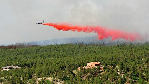 An aircraft releases fire-retardant over Black Forest, Colo.