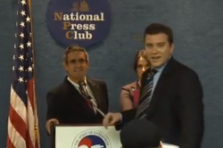 A Chamber of Commerce official interrupts a fake news conference by the Yes Men in 2009.