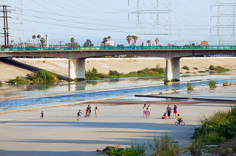 Families and kids in Maywood stroll along the LA River bed to keep cool on a hot Summer Sunday afternoon.