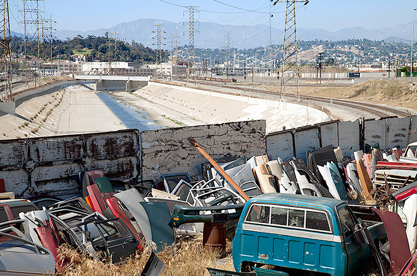 An auto scrap yard overlooks the downtown section of the LA River near Cesar Chavez Avenue.