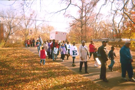 Community members march in the park.