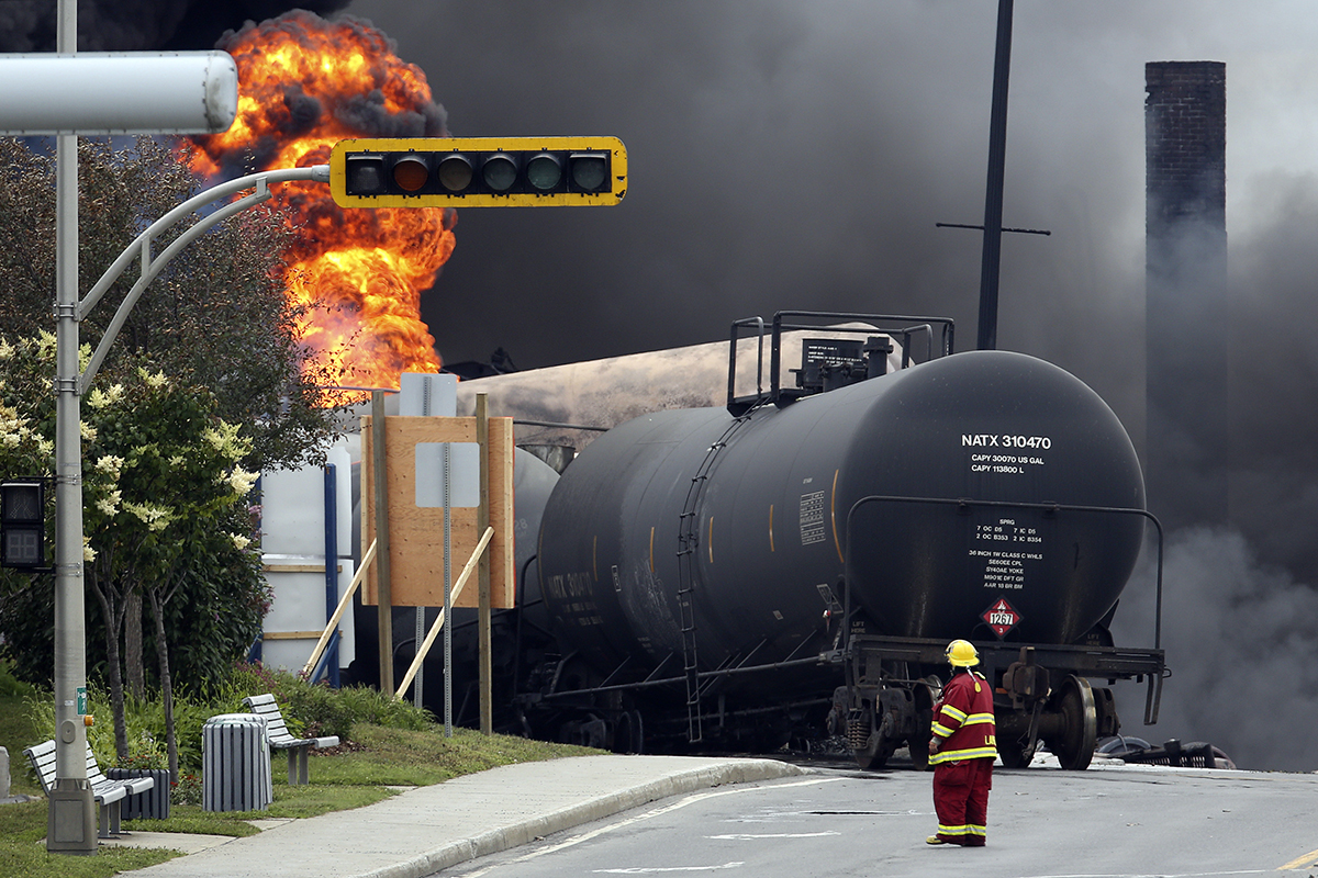 A firefighter walks past a burning train wagon at Lac Megantic, Quebec, July 6, 2013.