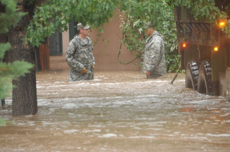 Two Colorado National Guardsmen waist deep in Boulder floodwaters.