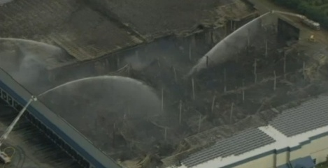 Firefighters spray what remains of the Dietz & Watson warehouse with water.