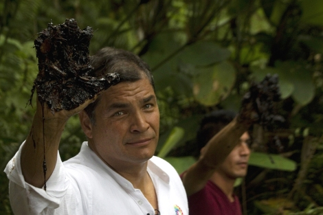 Ecuador's President Rafael Correa raises an oil-coated hand.