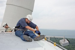 An engineer attaches an acoustic deterrent device to a turbine.