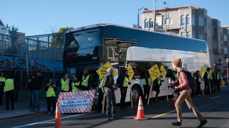 A Google bus surrounded by protestors.