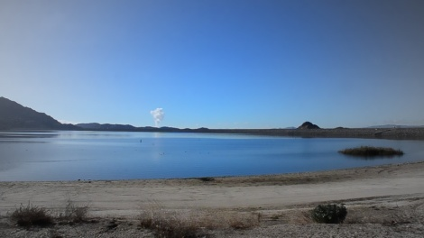 Water pours silently and invisibly into the Lake Perris reservoir.