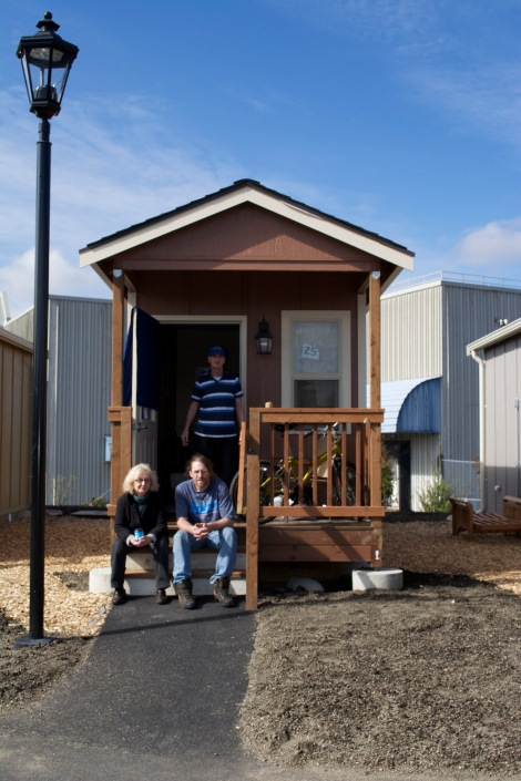 Quixote Village resident Robert Mitchell (standing) poses with Jill Severn (left, seated) and Jimi Christiansen (right, seated) on the porch of his house.