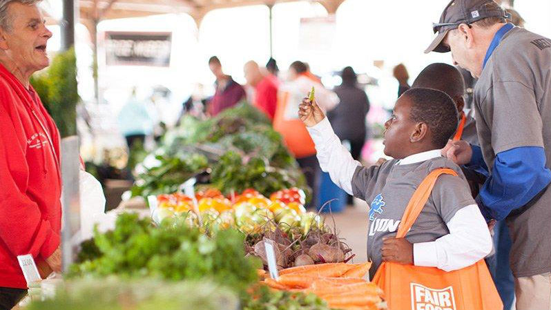 Oran Hesterman (at left). Photo from the Fair Food Network's partnership with the Detroit Lions and Eastern market working with kids from Detroit Public School