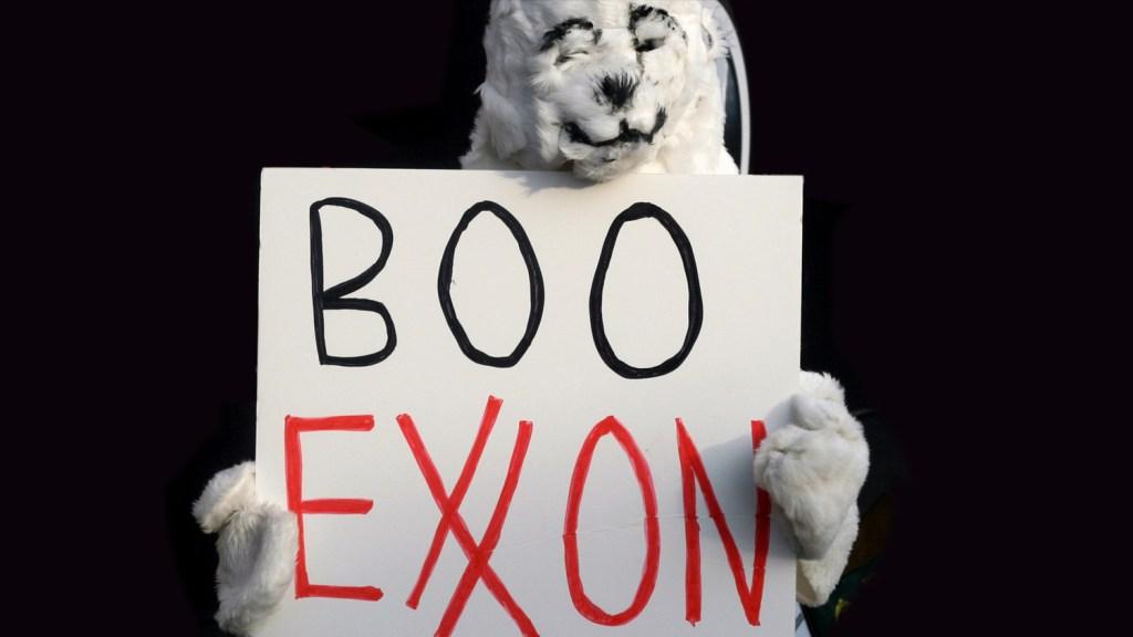 "protester with ""boo Exxon"" sign"