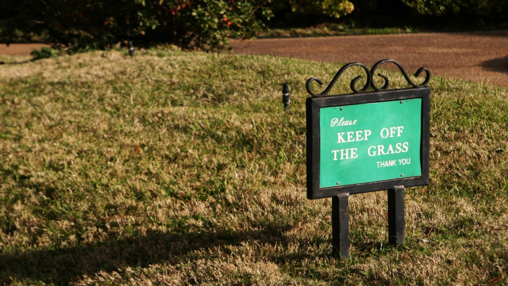 """""""keep off the grass"""" sign on browning lawn"""