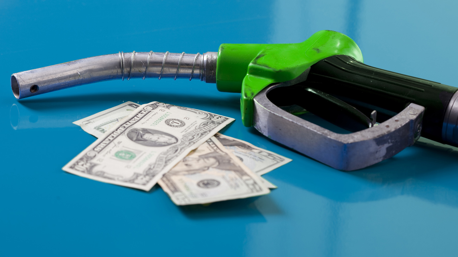 gas nozzle and dollar bills