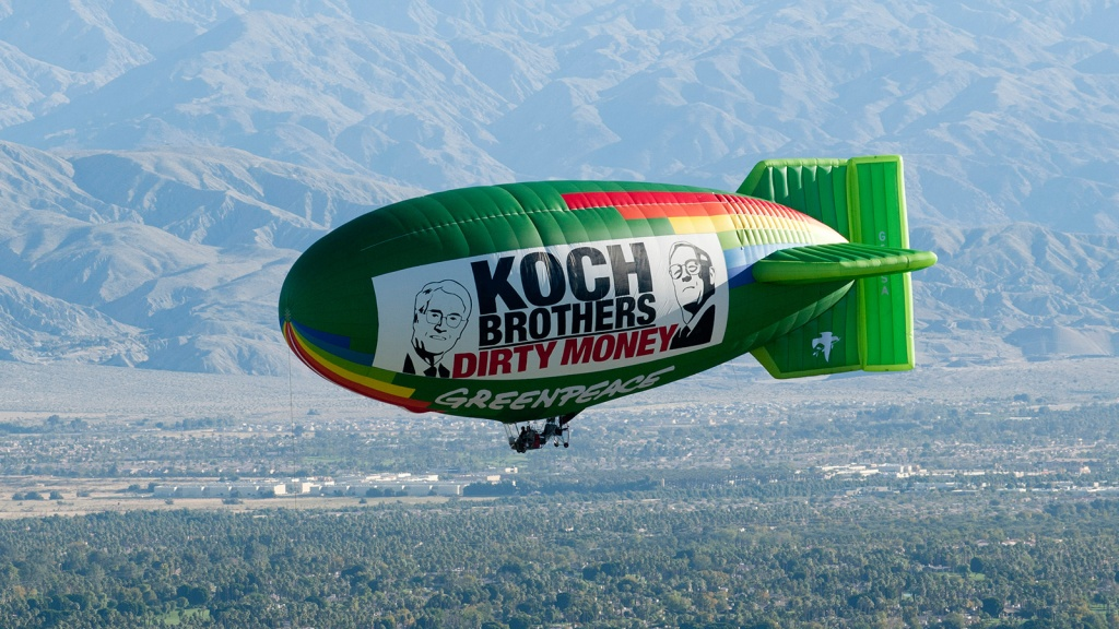 """The Greenpeace Airship A.E. Bates flies over the location of oil billionaires David and Charles Koch's latest secret political strategy meeting, with a banner reading """"Koch Brothers: Dirty Money."""""""