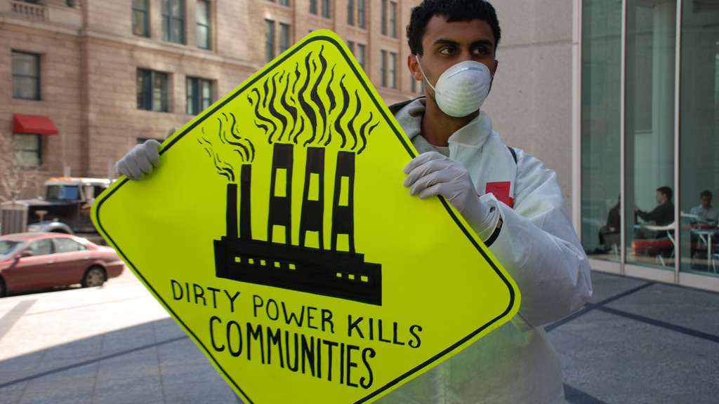 "activist with sign: ""Dirty power kills communities"""