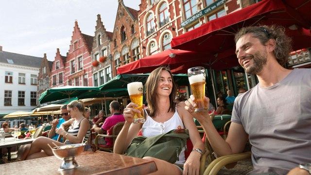 Couple having beer in Bruges, Belgium