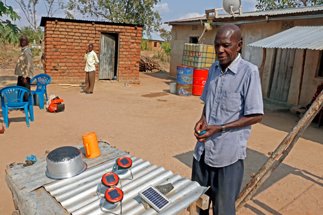Lusela Murandika is happy to have made the jump from diesel generator to solar. The panel that powers his TV is on the roof behind him, behind the satellite dish.