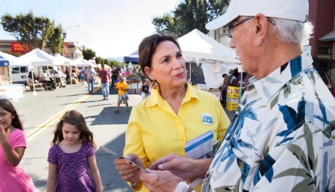 Margaret Morales Rebecchi hands out voter information on Measure J at the Hollister Farmers Market.
