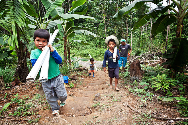 Waorani children haul components for clean-water systems to the village of Yawepare. Some of their homes are inside an oil block run by Andespetro, pollution from which flows into the Río Tiputini.