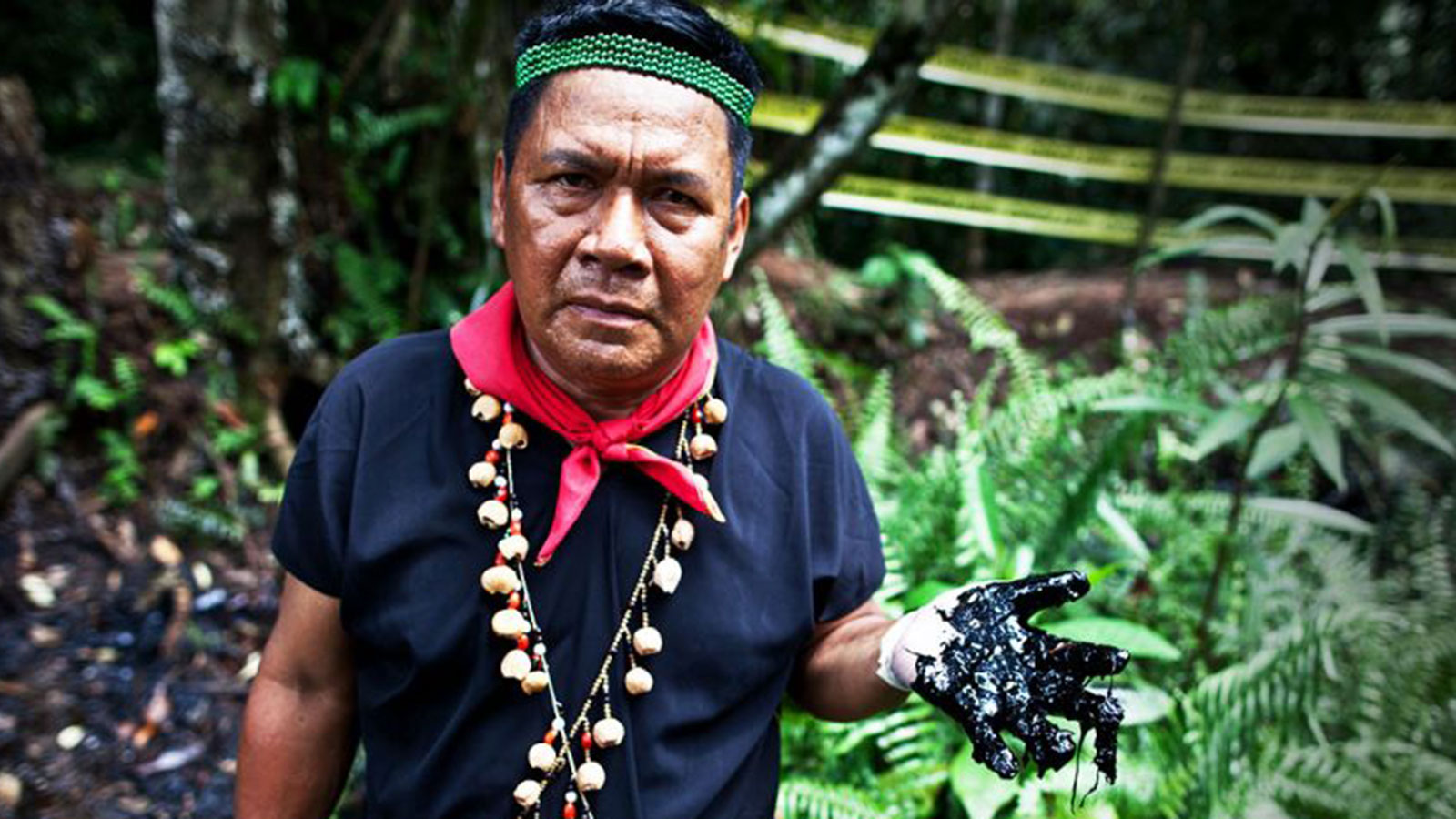 Amazonian man holds up hand full of oil.