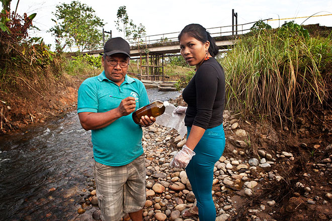 Emergildo Criollo and Nemonte Nenquimo take water samples downstream from a recent Petroamazonas oil spill that occurred just outside the town of Lago Agrio, in a tributary of the Río Aguarico.