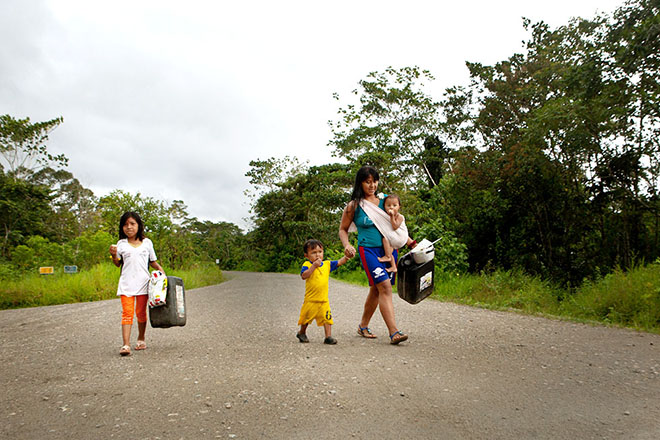 A family sets out along the Via Maxus, which cuts through Yasuní National Park, to collect water from a station operated by the Spanish company Repsol.
