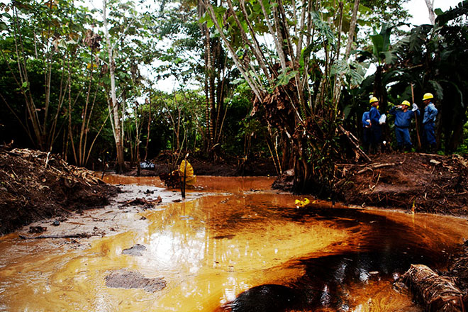 Petroamazonas workers observe a recent oil spill upriver from Emergildo Criollo's community, Cofán Dureno.