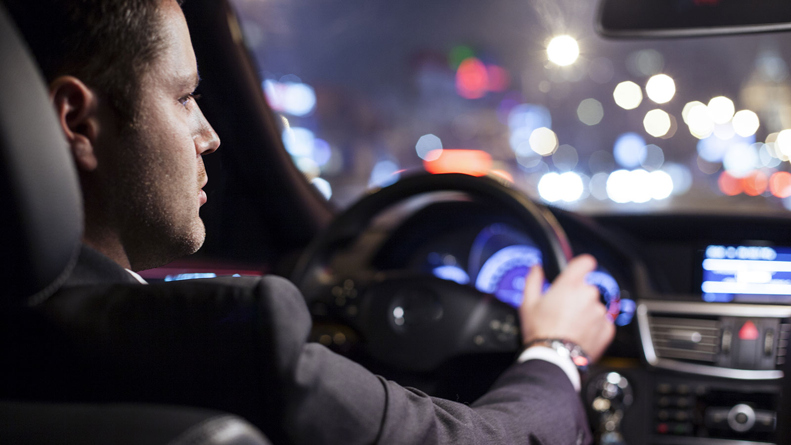 Businessman driving car at night