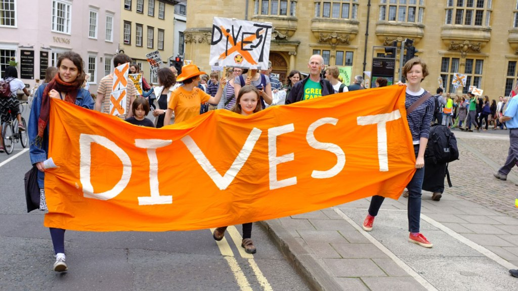 """activists with """"divest"""" banner"""