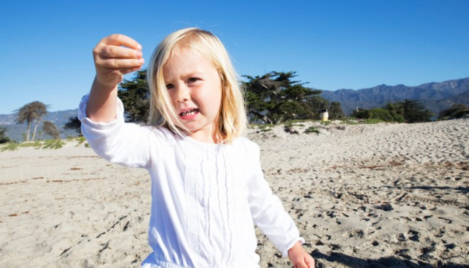 3-year-old Hazel stops to inspect a piece of beach debris.
