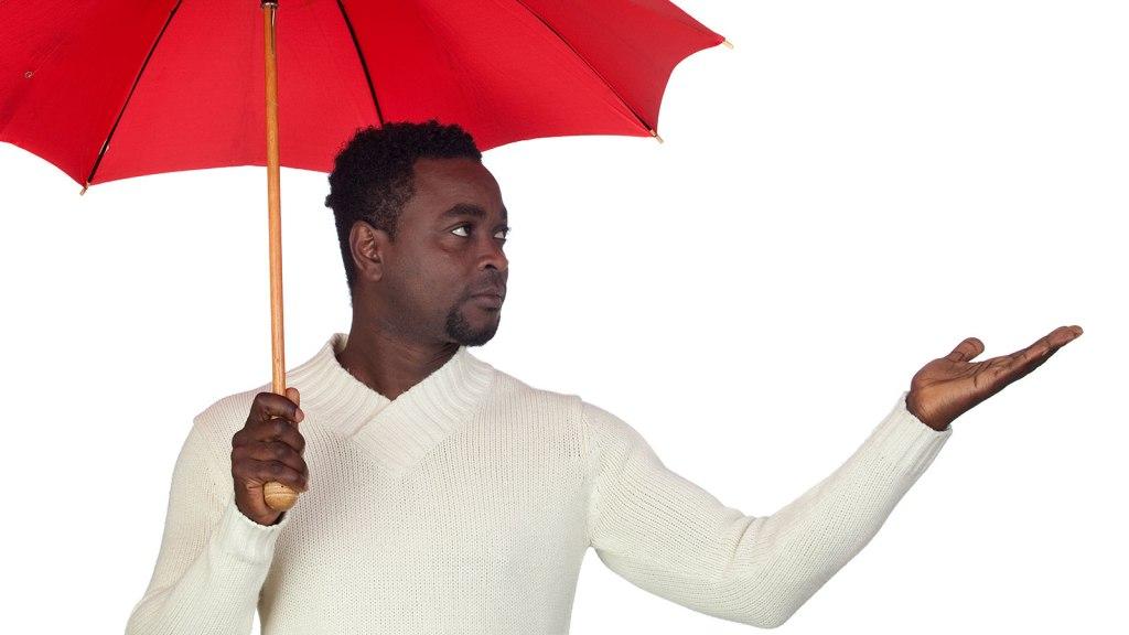 Man under umbrella, uncertain about rain