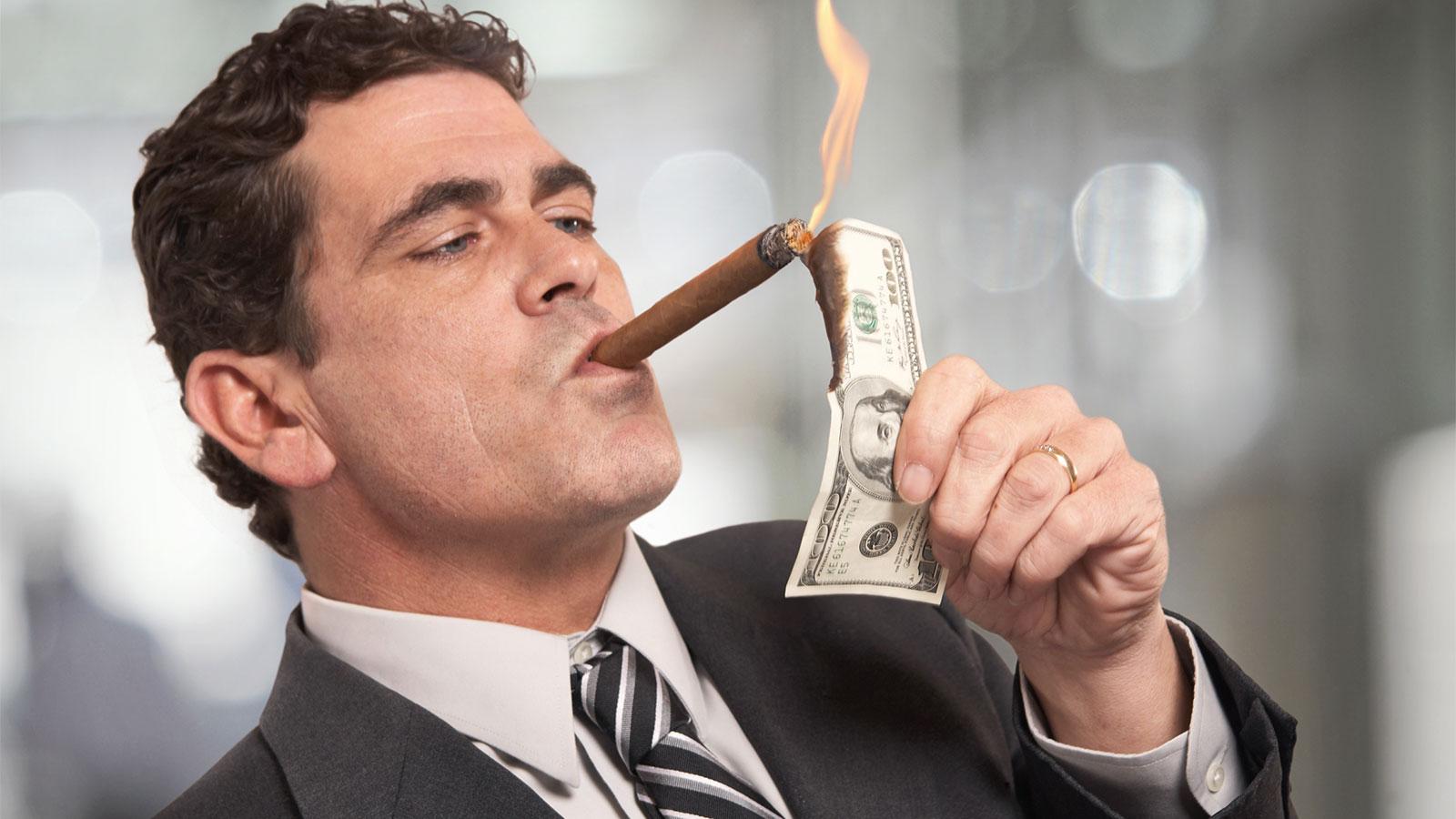 Man lighting cigar with $100 bill