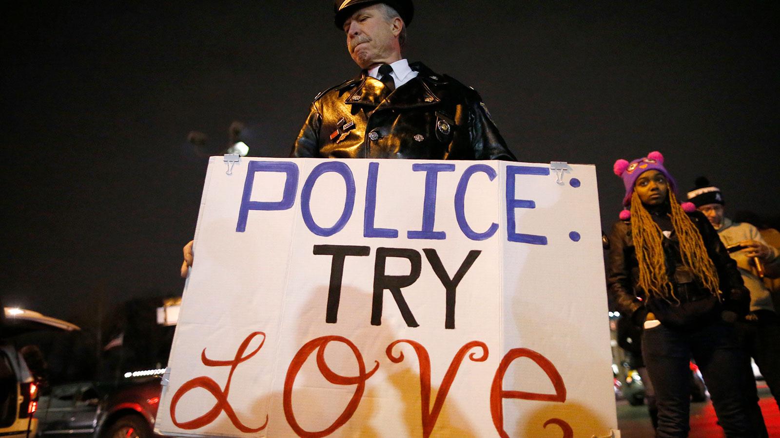 A man holds a sign outside the Ferguson Police Department in Ferguson, November 24, 2014.