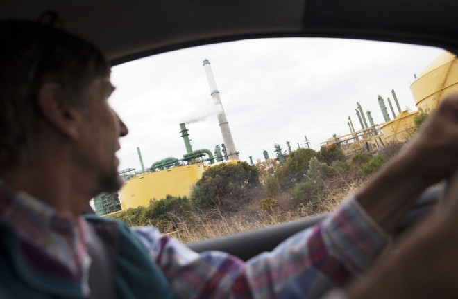 Ed Ruszel drives by the Valero Refinery, which is about a mile from his family's woodworking business in Benicia, CA.