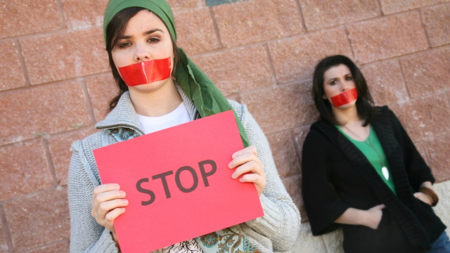 """censored activists with """"stop"""" sign"""
