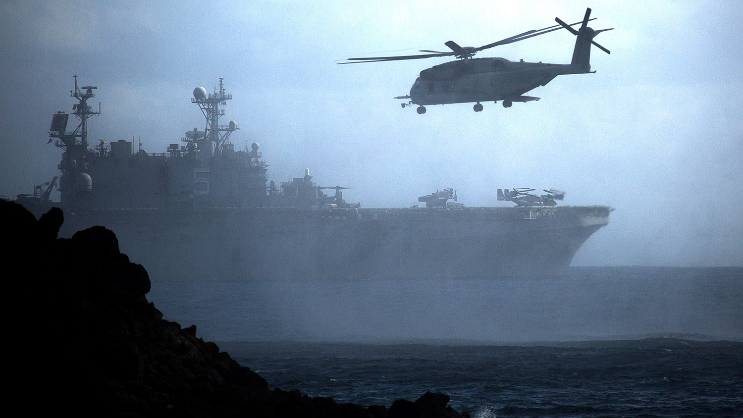 A CH-53E Super Stallion helicopter flies ahead of the amphibious assault ship USS Peleliu (LHA-5) after conducting helocast operations at Pyramid Rock Beach, Marine Corps Base Hawaii.