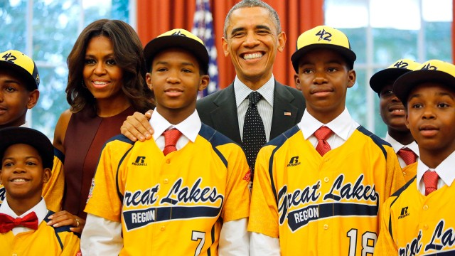 U.S. President Barack Obama and first lady Michelle Obama welcome members of the Jackie Robinson West All Stars Little League baseball team, including DJ Butler (bottom L), Lawrence Noble (#7), Eddie King (#18) and Jaheim Benton (far R), from Chicago in the Oval Office at the White House in Washington November 6, 2014. The team won the U.S. bracket of the Little League World Series this summer, before falling in the finals to the Seoul Little League of Seoul, South Korea.