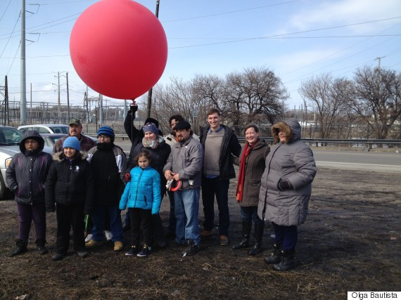 A group of area residents and activists poses with the weather balloon rig they are using to monitor petcoke operations in their neighborhood.