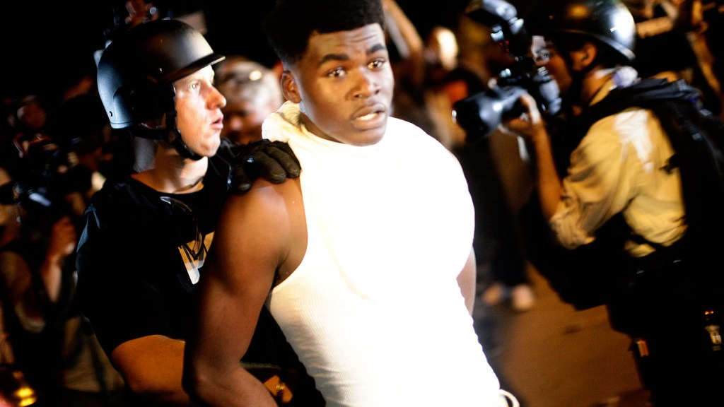 A police officer in riot gear detains a demonstrator protesting against the shooting of Michael Brown, in Ferguson, Missouri August 19, 2014.