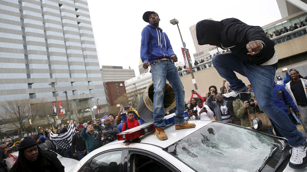 Protesters jump on a police car at a rally to protest the death of Freddie Gray who died following an arrest in Baltimore, Maryland April 25, 2015.